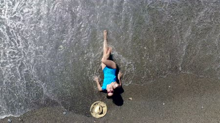 roupa de banho : A woman enjoys waves, lying on a beach.