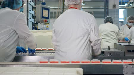 sterility : Crab sticks are getting removed from the conveyor by female factory workers.