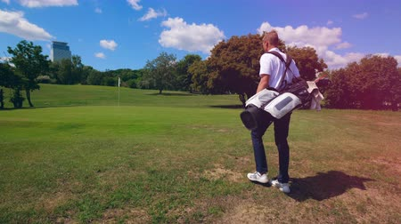 reszelt : Person walks on a golf filed, carrying a bag with equipment.