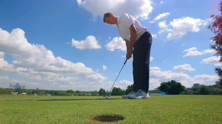 ゴルファー : Professional golfer hits a ball into hole on a grass field.