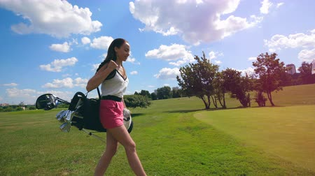 t şeklinde : Cheerful woman walks on a golf field, holding bag with clubs. Stok Video