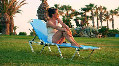 strandstoel : A lady is sitting in a deck-chair on a sunny beach