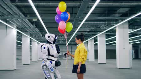 android : A girl and a robot are holding balloons together Stock Footage