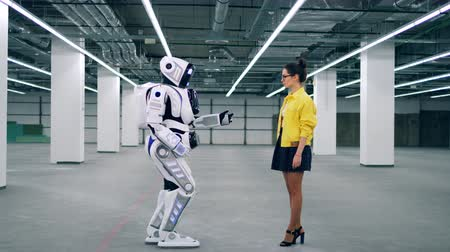 droid : Human-like robot is holding hands with a girl