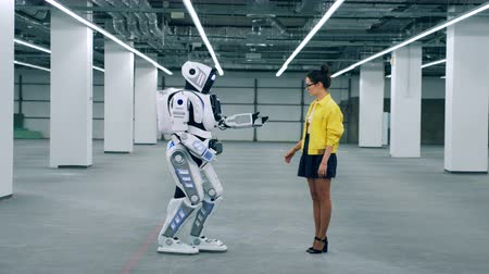 droid : A lady is giving her hand to a tall robot