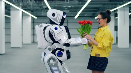 massif de fleurs : Tall robot is giving flowers to an excited girl Vidéos Libres De Droits