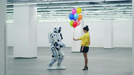 android : A girl is giving balloons to a cyborg in an empty hall