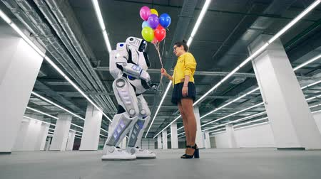 droid : Downside view of a cyborg accepting balloons from a lady Stock Footage