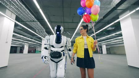 просторный : A lady and a robot are walking along the hall together