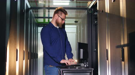 beheerder : Male IT programer, engineer works with a computer, standing in a server room. Stockvideo