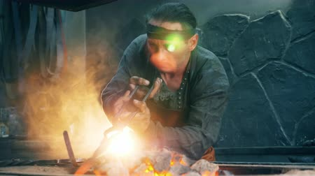 rabble : Male blacksmith is heating a metal instrument