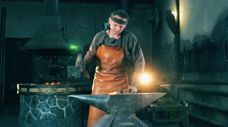 kowalstwo : Male blacksmith is hammering a metal tool Wideo