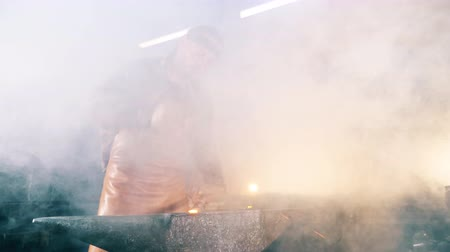 temperatura : Male blacksmith is forging a tool in clouds of smoke
