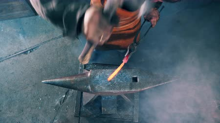 kowalstwo : Blacksmith is hammering a metal tool on the anvil