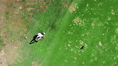 фарватер : One man kicks a ball while playing golf on a course.