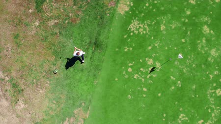 t şeklinde : Male golfer plays on a field, using a metal club.