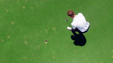 t şeklinde : Golfer hits a ball into a hole on a golfing field.