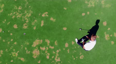 t şeklinde : Man puts ball in a hole while playing golf on a course.