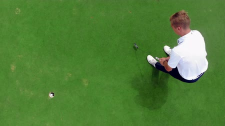 golfjátékos : A player hits a ball into a hole on a golfing field.