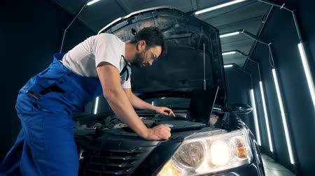 kaloryfer : Male mechanic is fixing a car with the help of a computer