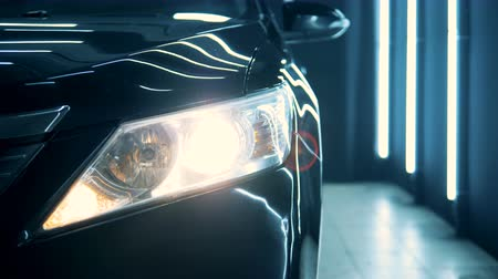 functioning : Switched-on headlight of a black car in a close up