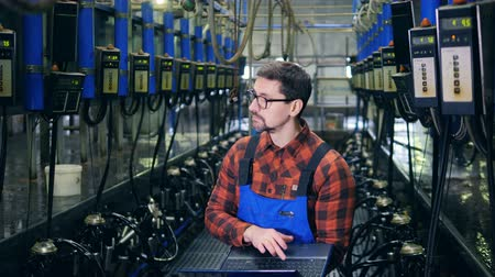 overall : An engineer examines farming machines in a cowshed, using a laptop.