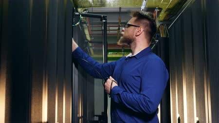arame : Male engineer is trying to plug a cable into servers Stock Footage