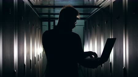 doména : Silhouette of an IT support engineer working with a laptop