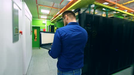 doména : Male computer technician is walking along the server unit
