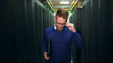 shluk : A man with a laptop is standing in a server room and fixing glasses