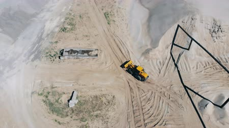 buldózer : Industrial site with a tractor driving along it in a top view. Mining equipment at quarry Stock mozgókép