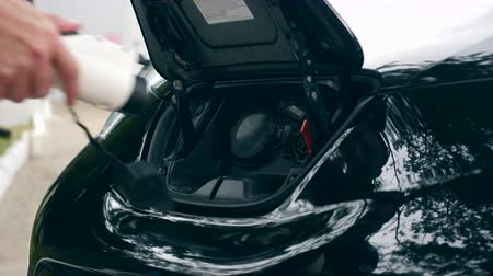 inovador : Black cars hood with an electrical nozzle during recharge