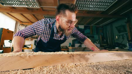 стружки : Carpenter removes wooden shavings from his table. Carpenter, craftsman working.