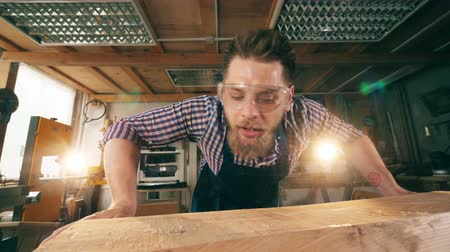 golenie : Joiner blows away wooden shavings from a table. Carpenter working.