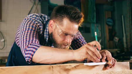 planking : Person works with wood, using pencil and a ruler. Carpenter working.