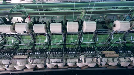 ボビン : Industrial machine with white threads on sewing bobbins. Textile factory facility. 動画素材