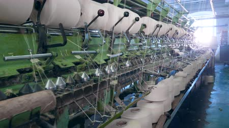 clothes line : Sewing loom with bobbins winding white threads. Modern textile factory.