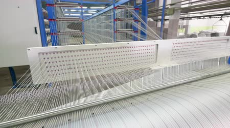 mechanically : Strings of white threads are rapidly relocating. Textile factory equipment.