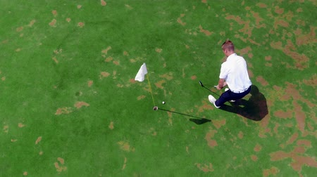 çimenli yol : A man puts a ball into a hole on a green course. Stok Video