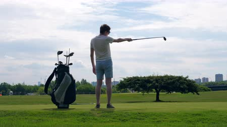 golfjátékos : A man is getting ready to start playing golf Stock mozgókép