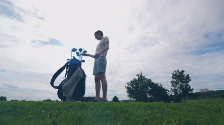 usado : Male player is choosing a golf club and getting used to it
