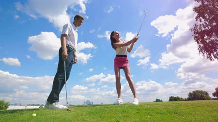 golfové hřiště : A man is teaching a lady to use a golf club Dostupné videozáznamy