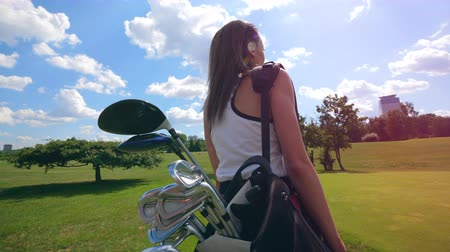 zadnice : Backside view of a woman walking with golf accessories