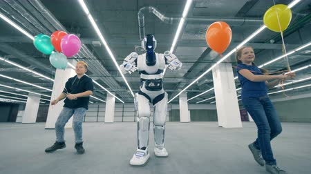 робот : Kids with balloons dancing with a droid, close up. School kid, education, science class concept.