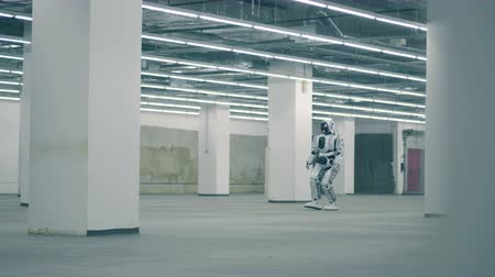 андроид : A robot walking in a room, close up.