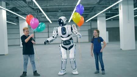 давать : Robot gives balloons to children, close up. School kid, education, science class concept.