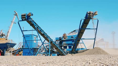 mijnwerker : Working machine crushes stones into rubble at a quarry. Mining industry concept.