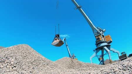 unload : Industrial crane carries rubble in a metal bucket.
