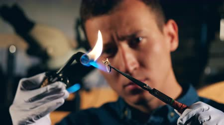designing : A silversmith is burning a ring with no stones Stock Footage