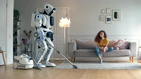 bot : Young woman is watching a robot hoovering a room